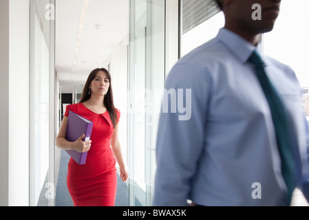Two business people walking past camera - Stock Photo