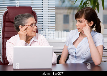 Profiles of aged woman and young female looking at each other seriously with laptop on the table - Stock Photo