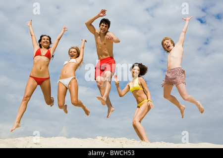 Portrait of friends in high jump over sandy shore against cloudy sky - Stock Photo