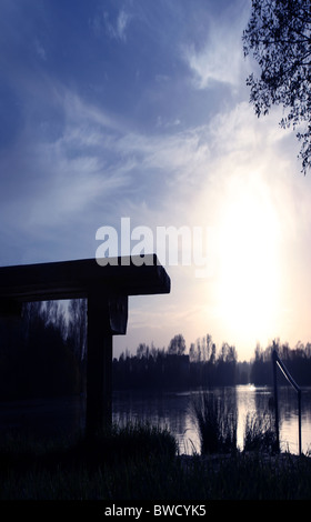 Empty bench overlooking a lake with the sun setting and reflecting on the water - Stock Photo