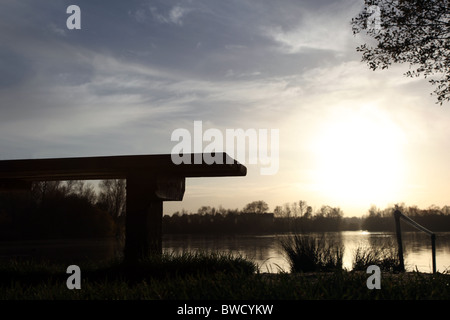 Empty bench overlooking a lake. - Stock Photo