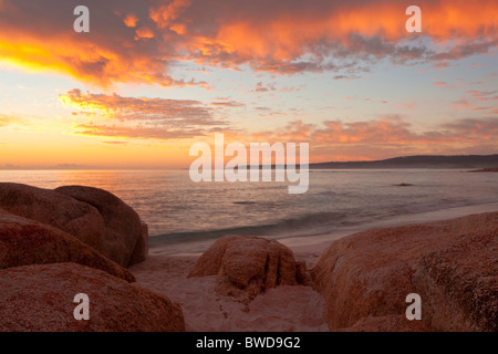 Sunrise over red lichen covered rocks at Cosy Corner in the Bay of Fires on Tasmania's East Coast - Stock Photo
