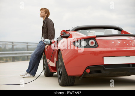 Young man filling up his electric car - Stock Photo