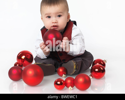 Six month old baby boy sitting with a red bauble Christmas decoration in his hands. Isolated on white background. - Stock Photo