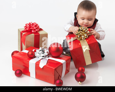 Six month old baby boy opening Christmas presents. Isolated on white background. - Stock Photo