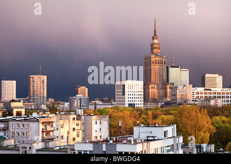 Warsaw, capital city of Poland, featuring Palace of Culture and Science, Srodmiescie district. Sunset time, stormy - Stock Photo