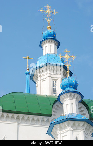 part of orthodox temple's roof and turrets with blue cupolas and golden orthodox crosses on top - Stock Photo