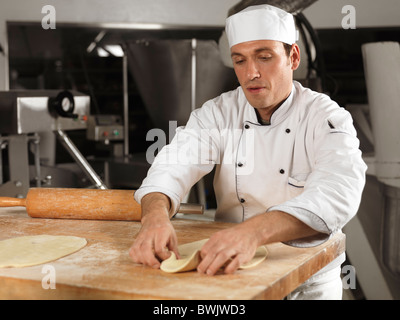 Baker rolling out dough in a bakery - Stock Photo