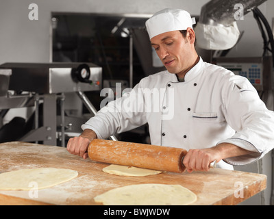 Baker rolling out dough with a rolling pin in a bakery - Stock Photo