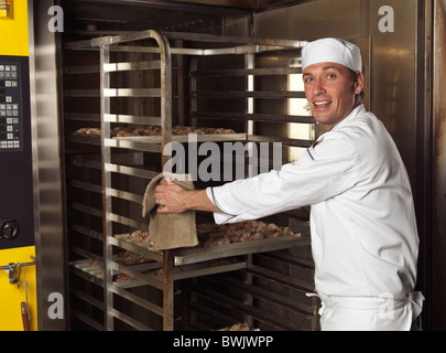Portrait of a baker taking out a rack trolley with freshly baked buns out of a bakery oven - Stock Photo