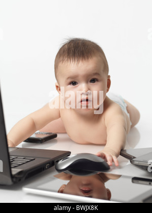 Six month old baby boy busy with computers and cell phones - Stock Photo