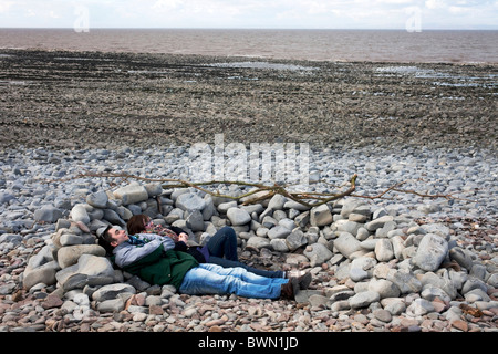 Couple lying down behind stones to keep out of the wind on a walk between Lilstock to Kilve in North Somerset.  - Stock Photo