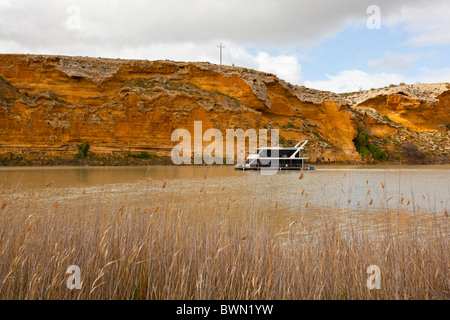 Houseboat cruising past golden cliffs on the Murray River at Walker Flat near Mannum in South Australia - Stock Photo