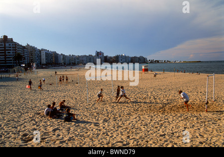 People on sandy shore in front of Montevideo beach front properties - Stock Photo