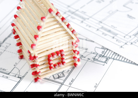 House made from matches standing on construction plans Construction industry Home renovation Real estate agency - Stock Photo