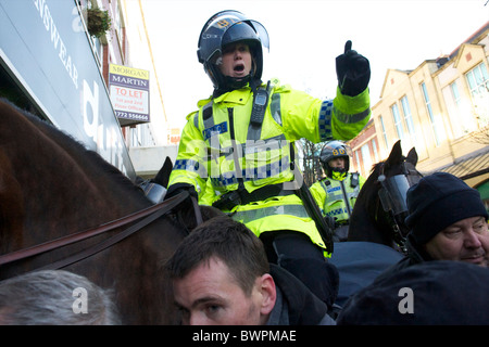 Police officers monitor members of the English Defence League (EDL) protesting in Preston, England on November 27, - Stock Photo