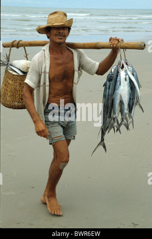 Brazil South America Jericoacoara State of Cearà fisherman fisher man carrying fish beach coast shore sea - Stock Photo