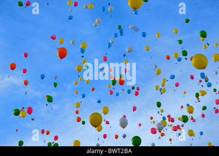 Brightly colored balloons floating across a blue sky. - Stock Photo