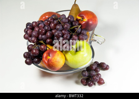 Stock photo of fruit bowl filled with grapes, apples, oranges and a pear. The bowl is apple shaped. - Stock Photo