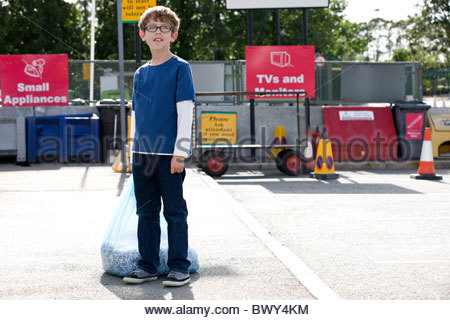 A young boy standing in a recycling centre, holding a bag of shredded paper - Stock Photo