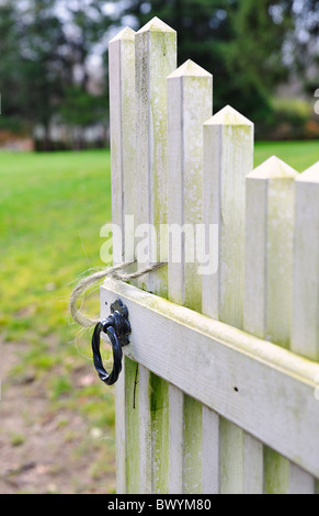 Old weathered open gate inviting you into the garden with selective focus shallow depth of field soft focus - Stock Photo