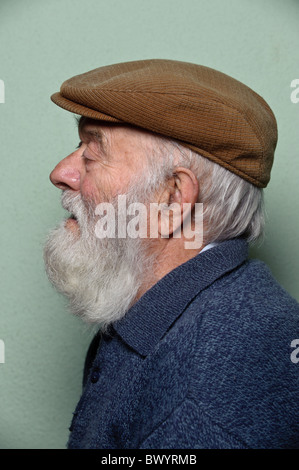 Isolated portrait of caucasian old man with long white beard wearing an hat - Stock Photo