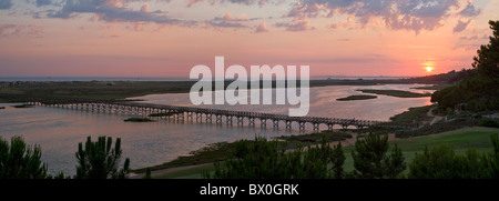 Portugal, the Algarve, sunset over the lagoon and the wooden bridge to the beach at Quinta do Lago - Stock Photo