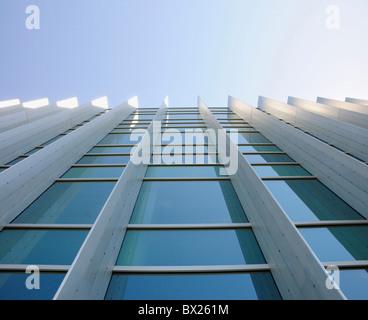 Exterior windows of a commercial office building looking up from the ground with blue sky reflected in windows - Stock Photo