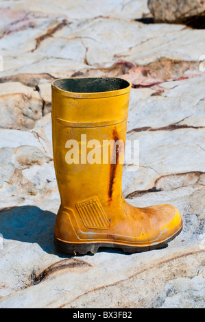 An old yellow wellington boot washed up on a rocky beach - Stock Photo