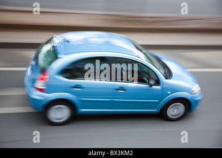 Small blue car speeding down street, high angle view, motion blur, Citroen C 3 - Stock Photo
