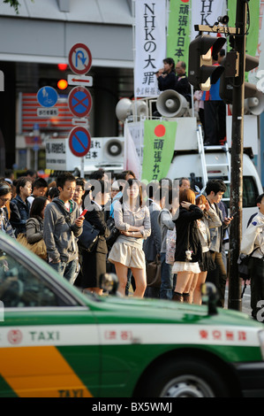 Young Japanese waiting at Shibuya Crossing in the evening sun, Tokyo, Japan - Stock Photo