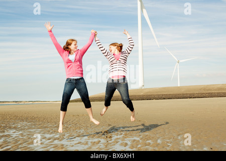 Two girls jumping on beach with turbines - Stock Photo