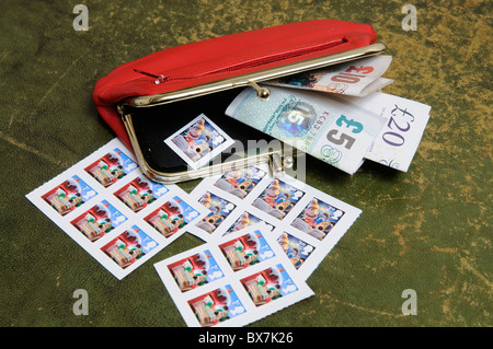 Cash in a red leather purse with Christmas theme British postage stamps - Stock Photo