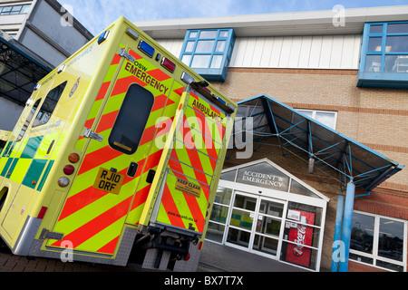 Emergency ambulance parked outside hospital accident and emergency entrance - Stock Photo