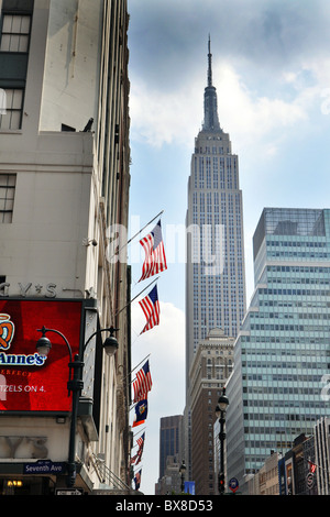 American flags fly outside Macy's Store on Seventh Avenue with the Empire State Building in the background - Stock Photo