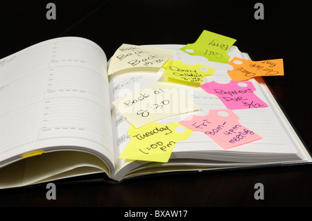 Adhesive notes stuck on a diary - Stock Photo