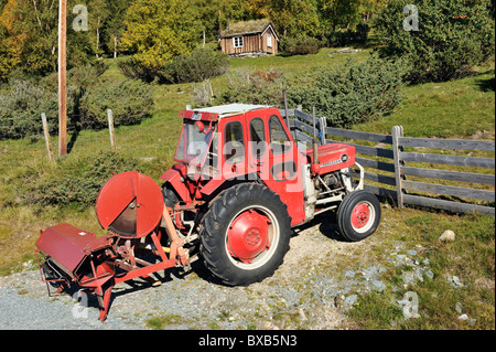 Tractor on dirt road, wooden house in the background - Stock Photo