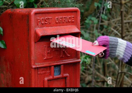 Woman posting Christmas greetings cards in a Royal Mail letterbox - Stock Photo