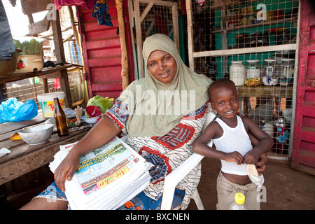 Ms. Bella Bah, shown with her son Taiub Saw, sells newspapers in Funkia neighborhood, Freetown, Sierra Leone, West - Stock Photo