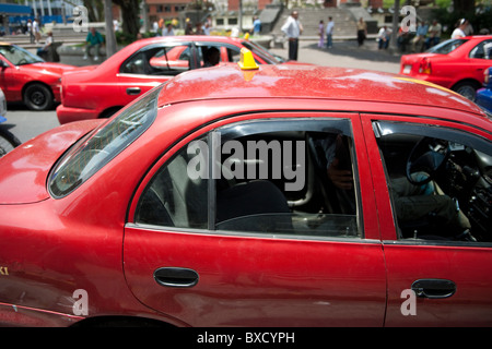 Red taxi cabs on a street in  San Jose, Costa Rica - Stock Photo