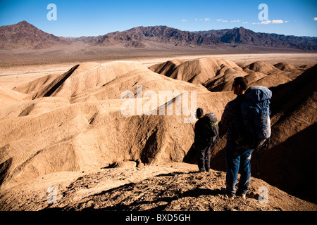 Two male hikers search to find the best route through Death Valley's Confidence Hills, in California, while on backing - Stock Photo
