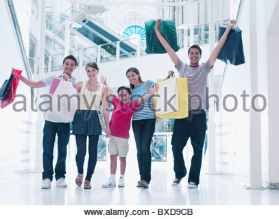 Happy family shopping together in mall - Stock Photo