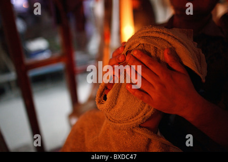 A man with a towel on his head in a barber shop in in Haridwar, Uttarakhand, India. - Stock Photo