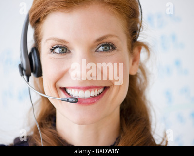 Cheerful businesswoman wearing headset - Stock Photo