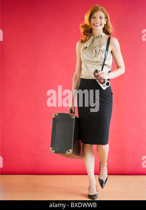Attractive woman carrying a suitcase - Stock Photo