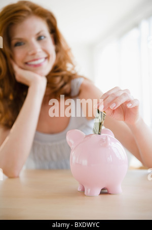Woman putting money in piggy bank - Stock Photo