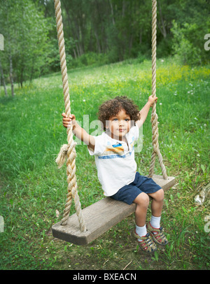 Young child sitting on large outdoor swing - Stock Photo