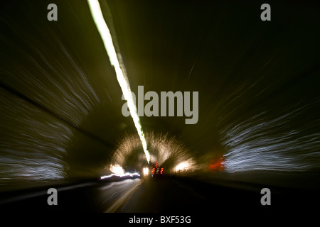 Car speeding through a tunnel with head lights and tail lights reflecting off  dome and sides of the tunnel - Stock Photo