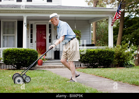 Senior man mowing his front lawn - Stock Photo