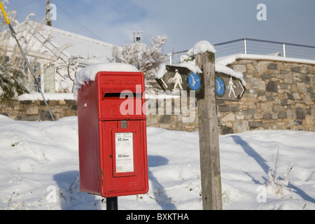 Isle of Anglesey North Wales UK December Red post box and Coastal Footpath sign covered in snow after unusually - Stock Photo